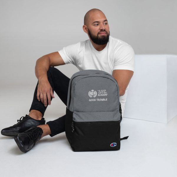 Man sitting with Heather Grey / Black Good Trouble backpack The Ashe Academy Store