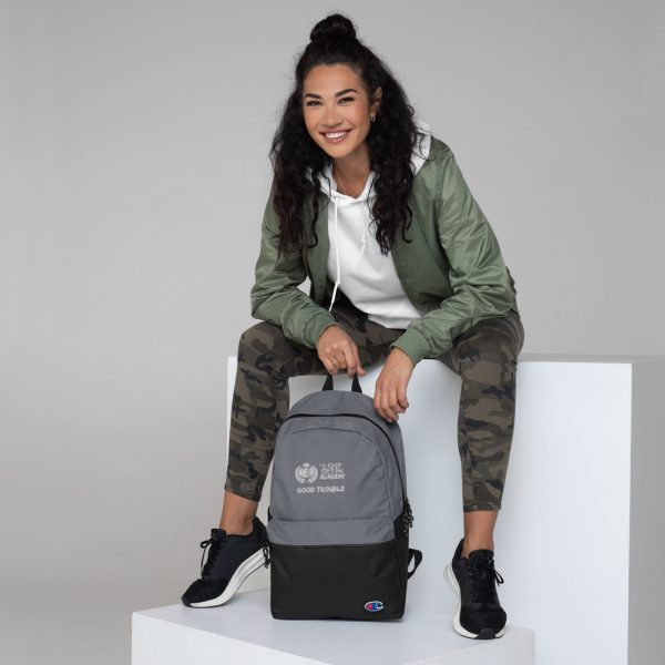 Woman sitting with Heather Grey / Black Good Trouble backpack The Ashe Academy Store