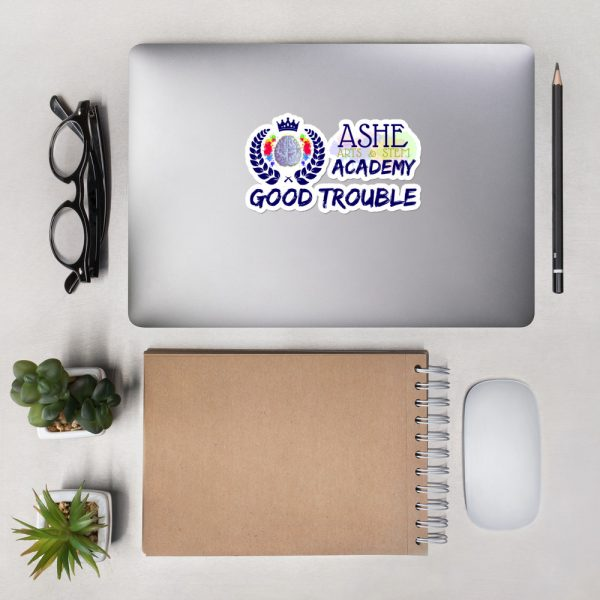 5.5x5.5 Good Trouble Sticker on laptop next to eyeglasses The Ashe Academy Store